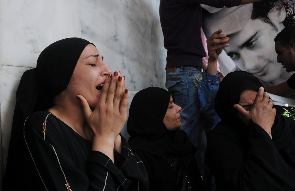 Photo -   Egyptian women mourn over the death of victims of clashes outside the Defense Ministry in Cairo, Egypt, Wednesday, May 2, 2012. Suspected supporters of Egypt's military rulers attacked predominantly Islamist anti-government protesters outside the Defense Ministry in Cairo Wednesday, setting off clashes that left more than ten people dead as political tensions rise three weeks before crucial presidential elections. (AP Photo/Mohammed Asad)