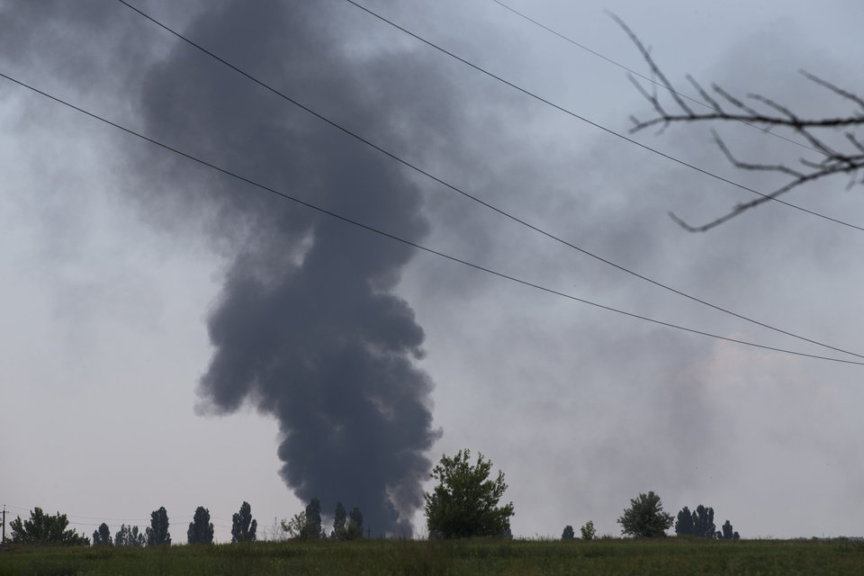 Photo - Black smoke rises from a shot down Ukrainian Army helicopter outside Slovyansk, Ukraine, Thursday, May 29, 2014. Rebels in eastern Ukraine shot down a government military helicopter Thursday amid heavy fighting around the eastern city of Slovyansk, killing 14 soldiers including a general, Ukraine's leader said. Acting President Oleksandr Turchynov told the parliament in Kiev that rebels used a portable air defense missile Thursday to down the helicopter and said that a General was among the dead. (AP Photo/Alexander Zemlianichenko)