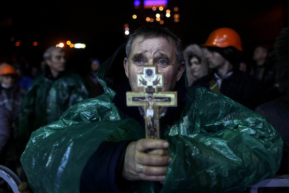 Photo - An anti-government protester holds a crucifix as he prays at Independence Square in Kiev, Ukraine, Thursday, Feb. 20, 2014. Ukraine's protest leaders and the president they aim to oust called a truce Wednesday, just hours after the military raised fears of a widespread crackdown with a vow to defeat