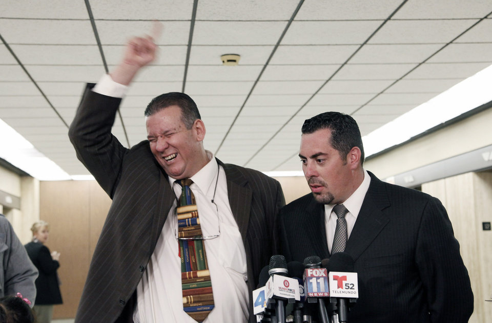Former Councilman Luis Artiga, left, celebrates his acquittal, standing with his attorney George Mgdesyan during a news conference after the Bell trial verdicts were read Wednesday March 20, 2013 in Los Angeles. Five former elected officials of the tiny California city of Bell were convicted Wednesday of multiple counts of misappropriation of public funds, and a sixth defendant, Artiga, was cleared entirely. (AP Photo/Nick Ut)