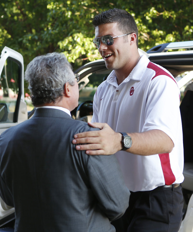 Photo - University of Oklahoma quarterback Blake Bell greets OU Club of Wichita President Mark Chamberlin at the Sooner Caravan at the Hyatt Wichita. Bell was there with head coach Bob Stoops and a few other coaches. Bell is a Wichita native and Bishop Carroll graduate. (June 19, 2013)  Photo by Jaime Green, The Wichita Eagle ORG XMIT: B73183861Z.1
