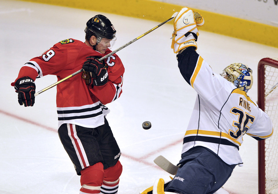 Photo - Chicago Blackhawks' Jonathan Toews, left, tries to tip in the puck as Nashville Predators' Pekka Rinne (35) blocks the shot during the second period of an NHL hockey game Monday, April 1, 2013, in Chicago. (AP Photo/Jim Prisching)