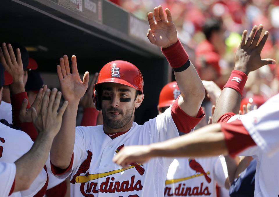 Photo - St. Louis Cardinals' Matt Carpenter is congratulated by teammates in the dugout after scoring on a three-run double by Kolten Wong during the second inning of a baseball game Sunday, May 18, 2014, in St. Louis. (AP Photo/Jeff Roberson)