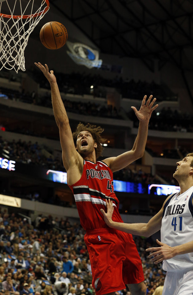 Photo - Portland Trail Blazers center Robin Lopez (42) shoots as Dallas Mavericks forward Dirk Nowitzki (41), of Germany, defends during the first half of an NBA basketball game on Friday, March 7, 2014, in Dallas. (AP Photo/John F. Rhodes)