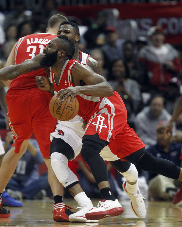 Houston Rockets shooting guard James Harden, foreground, drives against Atlanta Hawks point guard Devin Harris (34) in the first half of an NBA basketball game Friday, Nov. 2, 2012 in Atlanta. (AP Photo/John Bazemore)
