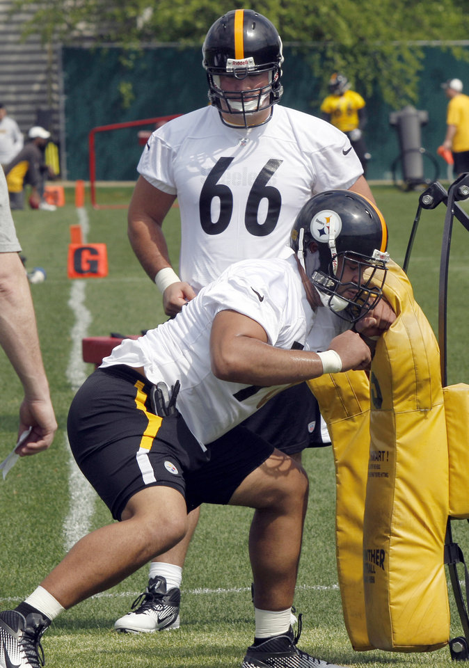 Photo -   Pittsburgh Steelers second round draft choice, offensive tackle from Ohio State Mike Adams, bottom, does a blocking drill as their number one draft choice, David DeCastro (66), an offensive guard from Stanford, watches during the NFL football team's rookie minicamp at their facility in Pittsburgh on Friday, May 4, 2012. (AP Photo/Keith Srakocic)