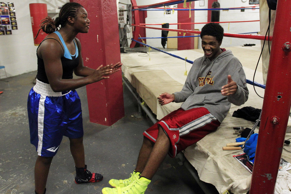 Photo -   In this Sept. 18, 2012, photo, Olympic gold medal boxer Claressa Shields shares a laugh with training partner Ardreal Holmes at the Berston Field House in Flint, Mich. Aside from her Olympic title and a jab that could knock someone out cold, Shields isn't much different than other high school seniors. (AP Photo/Carlos Osorio)
