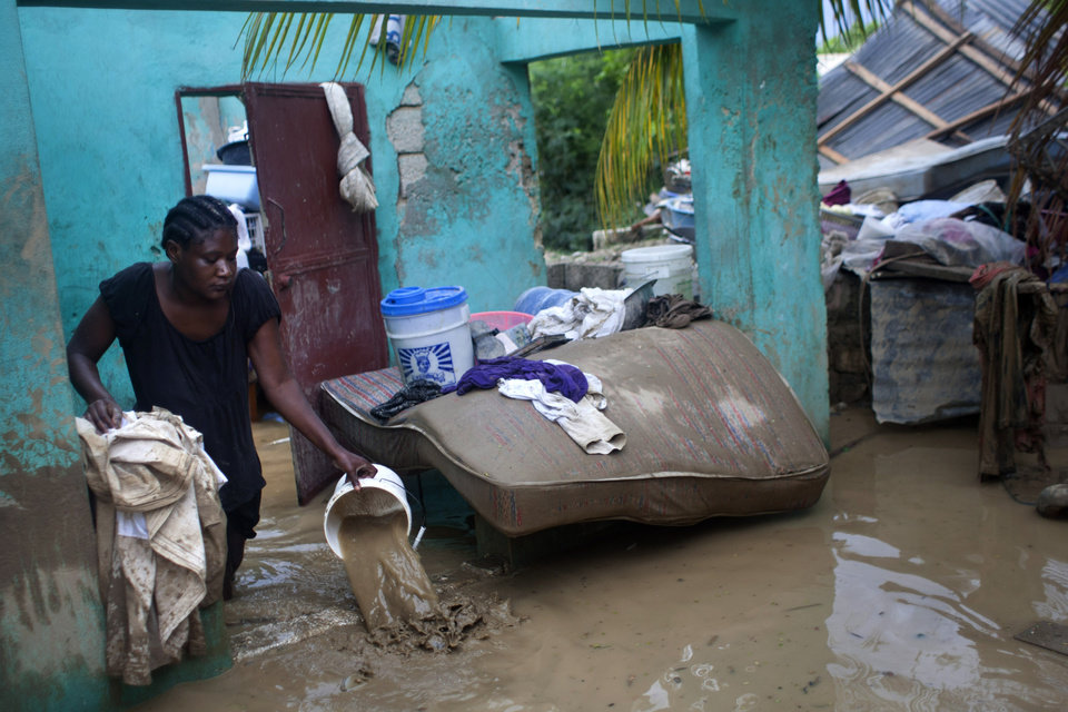 Finanette Guerrier 29, bails muddy water from her flooded house after the passing of Tropical Storm Isaac in Port-au-Prince, Haiti, Sunday Aug. 26, 2012. The death toll in Haiti from Tropical Storm Isaac has climbed to seven after an initial report of four deaths, the Haitian government said Sunday. (AP Photo/Dieu Nalio Chery) ORG XMIT: PAP105