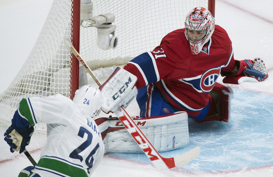Photo - Montreal Canadiens goaltender Carey Price makes a save against Vancouver Canucks' Raphael Diaz during the second period of an NHL hockey game Thursday, Feb. 6, 2014, in Montreal. (AP Photo/The Canadian Press, Graham Hughes)