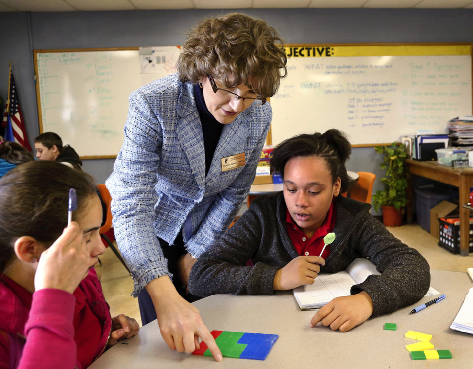 Photo - Heather Sparks uses plastic pieces as she helps two girls understand a math problem where they were asked to determine the area of a shape in a math class at Taft Middle School on Thursday, Jan. 30, 2014. Story about high poverty in the Oklahoma City school district and how it can affect the  learning process if a child comes to class  hungry, not clothed properly or without adequate sleep due to issues related to poverty. Photo by Jim Beckel, The Oklahoman