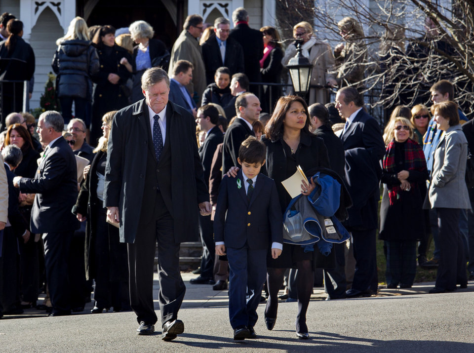 A young mourner is escorted from the funeral of teacher Anne Marie Murphy at the St. Mary Of The Assumption Church in Katonah, N.Y. Thursday, Dec. 20, 2012. Murphy was killed when Adam Lanza, walked into Sandy Hook Elementary School in Newtown, Conn., Dec. 14, and opened fire, killing 26, including 20 children, before killing himself. (AP Photo/Craig Ruttle)