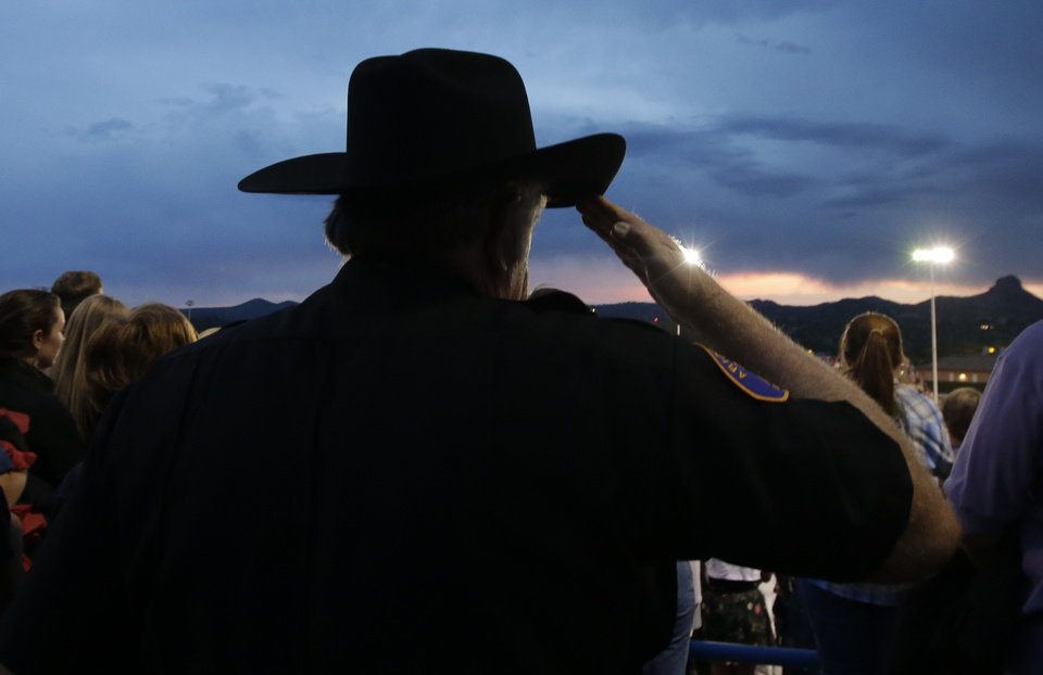 Photo - An Arizona Ranger salutes during a community vigil on Tuesday, July 2, 2013.  in Prescott, Ariz. for the 19 firefighters from Granite Mountain Interagency Hotshot Crew that were killed battling a wildfire near Yarnell, Ariz. The elite crew of firefighters were overtaken by the out-of-control blaze as they tried to protect themselves from the flames under fire-resistant shields on Sunday. (AP Photo/Chris Carlson)