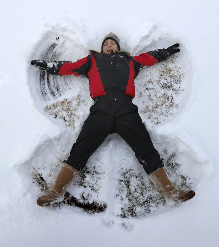 Photo - Costa Rican resident Noelia Vega experiences her first snow while making a snow angel, as a snowstorm dumps several inches in Edmond, Okla. Friday, Jan. 6, 2017.  Photo by Paul Hellstern, The Oklahoman