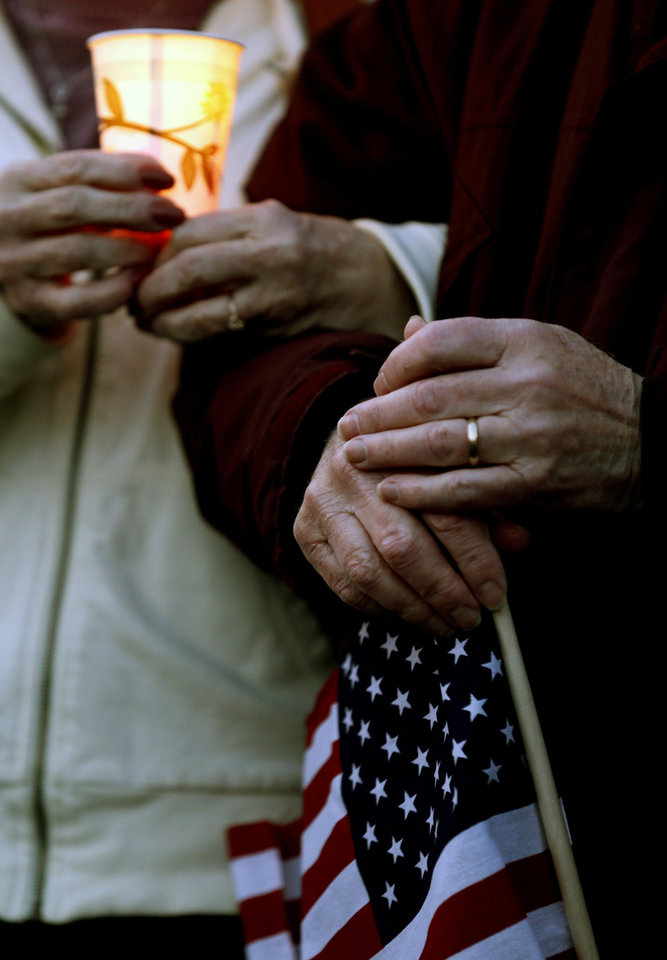 Photo - Judy Pannesi, 67, left, and George Kenrick, 72, who met during a vigil for the victims of the Boston Marathon bombing, interlock arms during a moment of silence, Saturday, April 20, 2013, in Watertown, Mass. Suspected bomber Dzhokhar Tsarnaev is hospitalized in serious condition with unspecified injuries after he was captured in an all day manhunt the day before. (AP Photo/Julio Cortez)