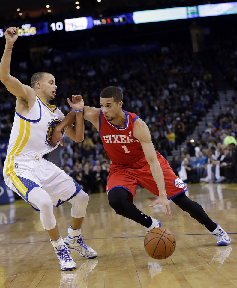 Photo - Philadelphia 76ers' Michael Carter-Williams (1) dribbles next to Golden State Warriors' Stephen Curry during the first half of an NBA basketball game, Monday, Feb. 10, 2014, in Oakland, Calif. (AP Photo/Marcio Jose Sanchez)
