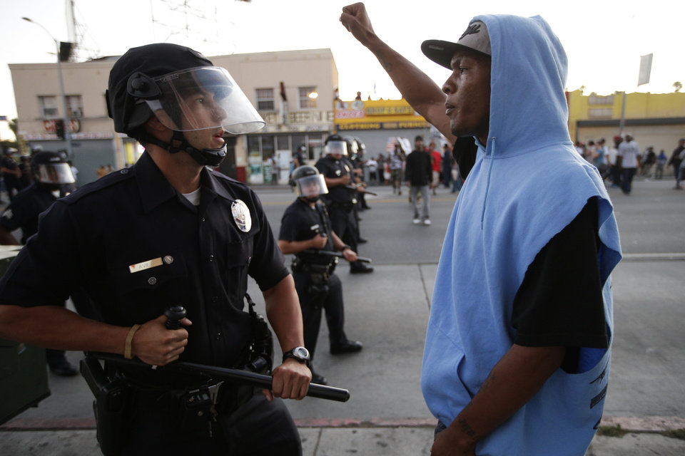 Photo - A protester confronts a Los Angles police officer during a demonstration in reaction to the acquittal of neighborhood watch volunteer George Zimmerman on Monday, July 15, 2013, in Los Angeles. Anger over the acquittal of a U.S. neighborhood watch volunteer who shot dead an unarmed black teenager continued Monday, with civil rights leaders saying mostly peaceful protests will continue this weekend with vigils in dozens of cities. (AP Photo/Jae C. Hong)