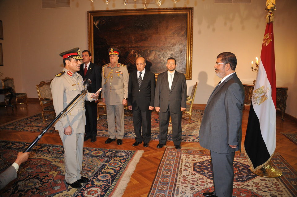 Photo -   Egyptian President Mohammed Morsi, left, swears in newly-appointed Minister of Defense, Lt. Gen. Abdel-Fattah el-Sissi, in Cairo, Egypt, Sunday, Aug. 12, 2012. Egypt's Islamist president ordered his former defense minister and chief of staff to retire on Sunday and canceled the military-declared constitutional amendments that gave top generals wide powers. (AP Photo/Egyptian Presidency)