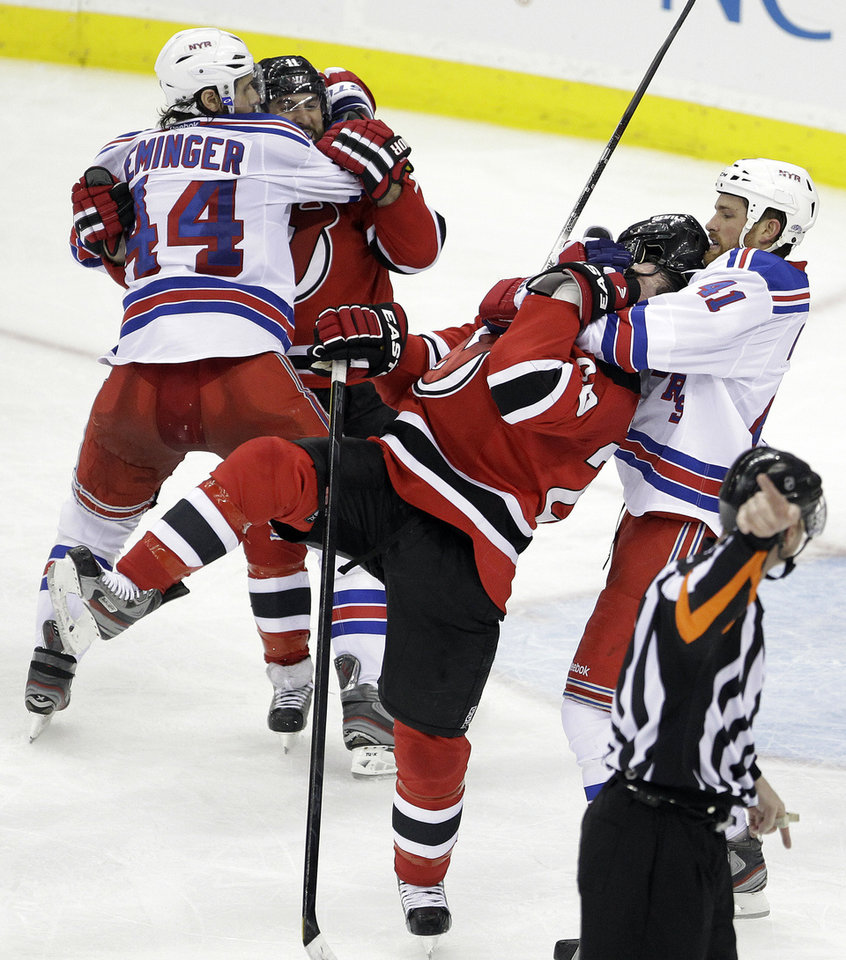 Photo -   New York Rangers' Stu Bickel, right, grabs at New Jersey Devils' Ryan Carter, center, as Rangers' Steve Eminger, left, grabs Stephen Gionta during a scuffle in the third period of Game 4 of an NHL hockey Stanley Cup Eastern Conference final playoff series, Monday, May 21, 2012, in Newark, N.J. The Devils won 4-1. (AP Photo/Julio Cortez)