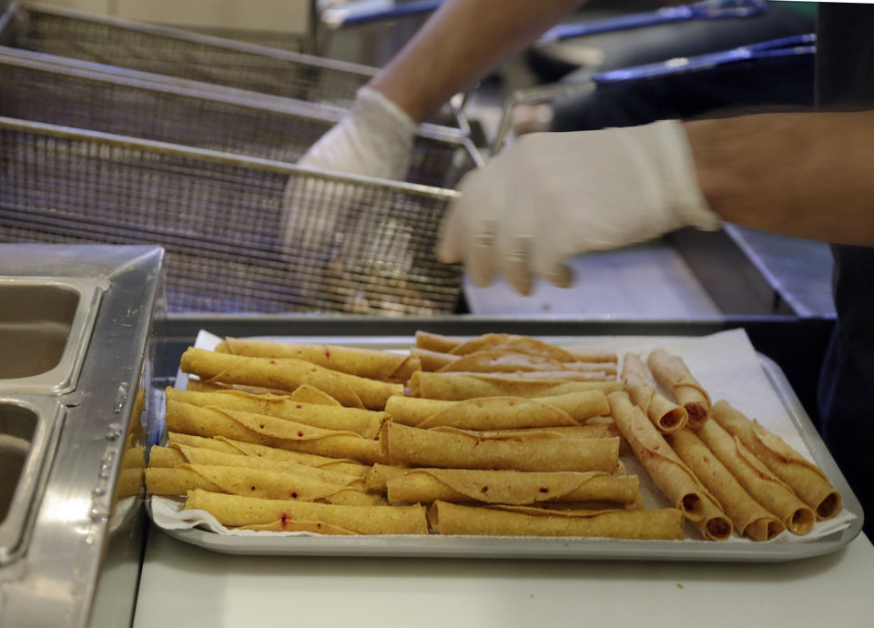 Photo - Buffalo chicken taquitos are removed from a fryer at Taquitoria, on New York's Lower East Side,Tuesday, Jan. 14, 2014. Taquitoria, a shop that serves only the deep-fried, cigar-like tortillas called taquitos, offers 40-piece boxes of the Buffalo chicken taquitos throughout football season. On Super Bowl game day they expect to do 99 percent of their business for takeout. (AP Photo/Richard Drew)