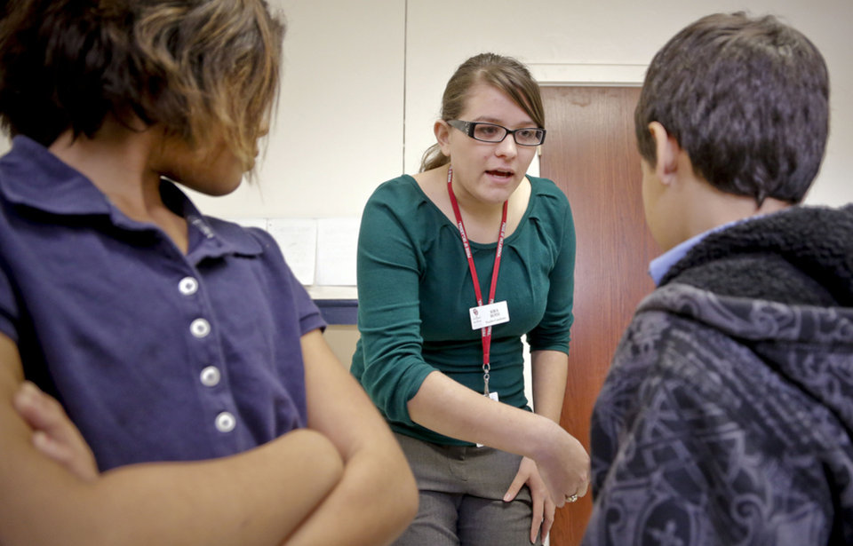Photo - Student teacher Kira Roth works with fifth-grade students at Putnam Heights Elementary School. Roth is working full-time at the school as part of the Urban Teacher Preparation Academy. The UTPA trains education majors to be more effective teachers in urban settings. PHOTO BY CHRIS LANDSBERGER, THE OKLAHOMAN  CHRIS LANDSBERGER - CHRIS LANDSBERGER