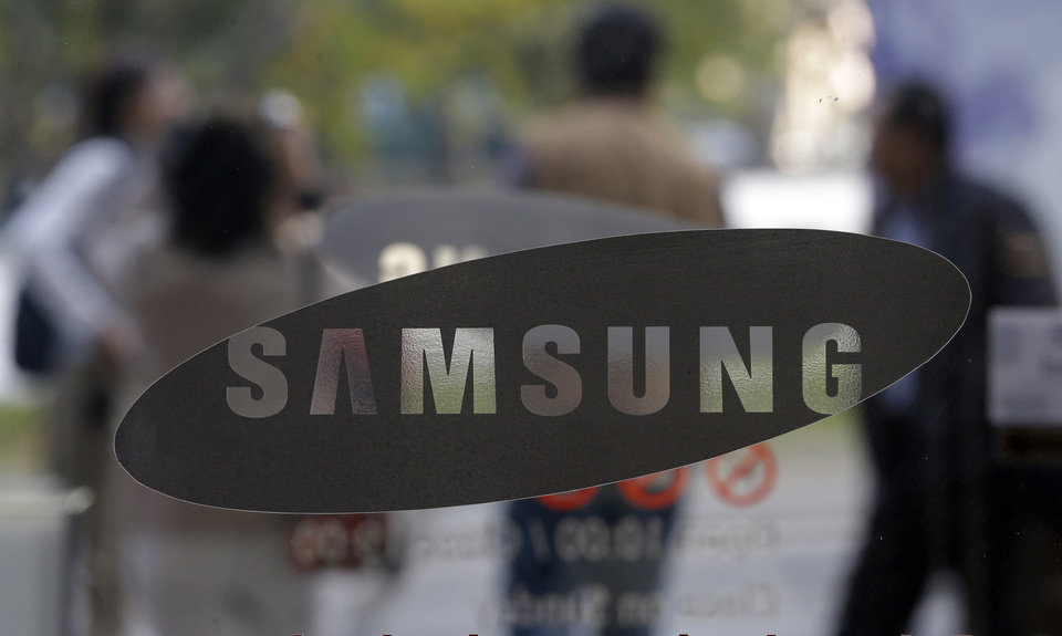 Photo -   Visitors walk by the entrance to the Samsung Electronics Co. showroom at its headquarters in Seoul, South Korea, Friday, Oct. 26, 2012. Samsung's third-quarter net profit nearly doubled over a year earlier to a record high propelled by strong sales of Galaxy phones that helped widen its lead over rivals. (AP Photo/Lee Jin-man)