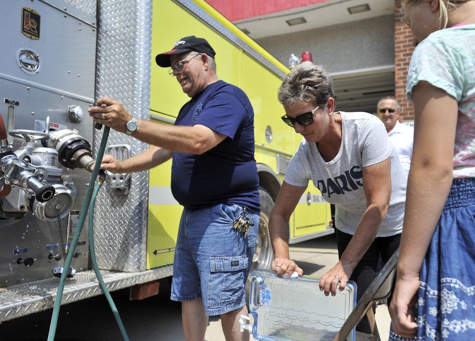 Photo - Luna Pier, Mich, fire department Lt. Warren Rains, left, puts the hose back while Brenda Badger of Erie, Michigan closes the container that was just filled with water at the Luna Pier fire station, Aug. 3, 2014. Four communities in Monroe County, Michigan were told to not use their water due to toxins in the Toledo water distribution system.   (AP Photo/Detroit News, Robin Buckson )  DETROIT FREE PRESS OUT; HUFFINGTON POST OUT   MANDATORY CREDIT
