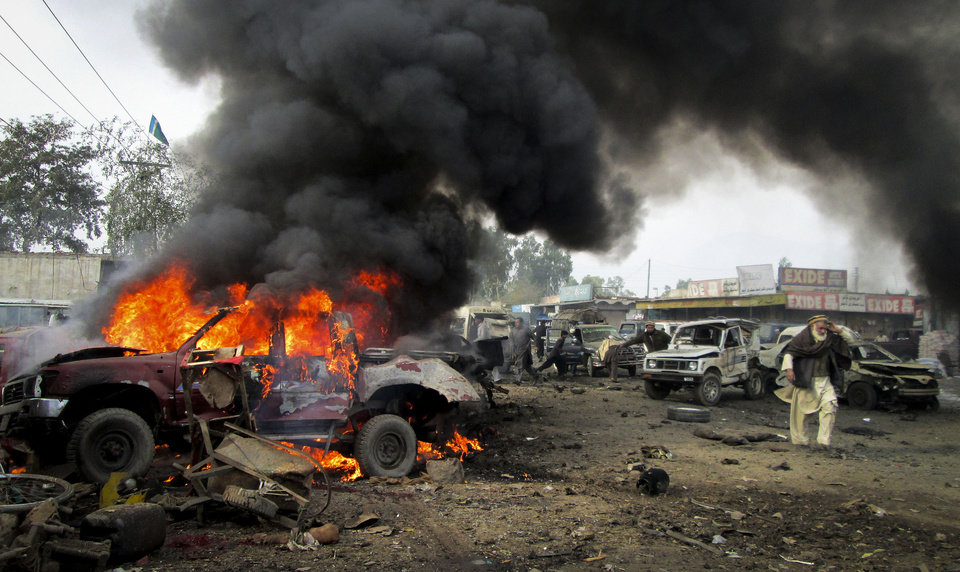 Photo - A Pakistani man walks past a burning vehicle after a blast in the Pakistani tribal area of Khyber, Monday, Dec. 17, 2012. A car bomb exploded outside the women's waiting area of a government office in Pakistan's troubled northwest tribal region, killing many people and wounding others, government officials said. (AP Photo/Qazi Rauf)