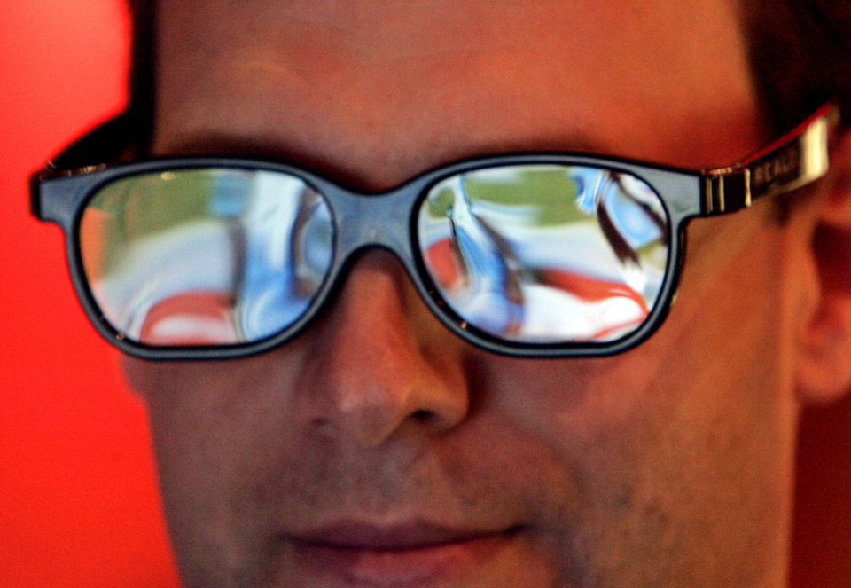 Photo - The picture is reflected in special 3-D viewing glasses as Glenn Lorenz, of Los Angeles, watches the Oakland Raiders play the San Diego Chargers on a big screen television in Los Angeles on Thursday, Dec. 4, 2008. Also seen simultaneously at theaters in New York and Boston, promoters promise an
