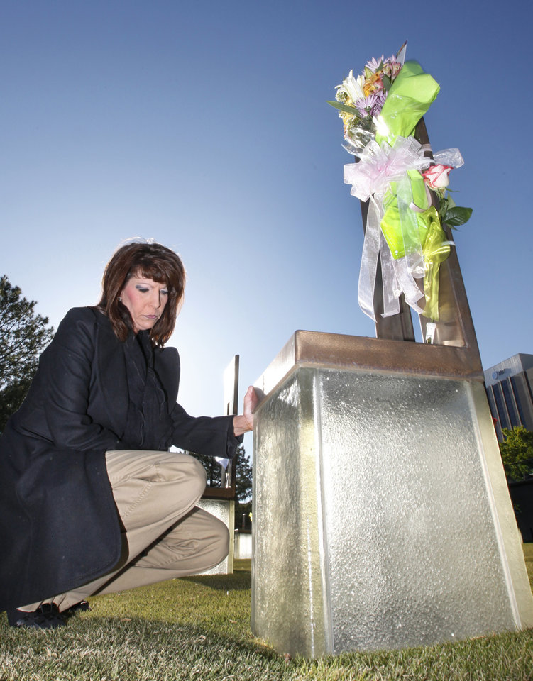 Photo - Shelly Thompson Fravert kneels by her mother Virginia Thompson's chair during the 18th Anniversary Remembrance Ceremony at the Oklahoma City National Memorial and Museum, Friday, April 19, 2013. Photo By David McDaniel/The Oklahoman