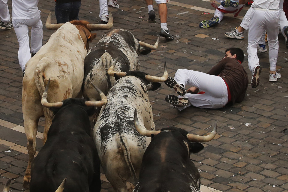 Photo - A reveler falls as a Torrestrella fighting bulls run during the running of the bulls of the San Fermin festival, in Pamplona, Spain, Monday, July 7, 2014. Revelers from around the world arrive to Pamplona every year to take part on some of the eight days of the running of the bulls glorified by Ernest Hemingway's 1926 novel