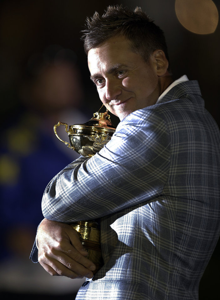 Europe's Ian Poulter hugs the trophy after winning the Ryder Cup PGA golf tournament Sunday, Sept. 30, 2012, at the Medinah Country Club in Medinah, Ill. (AP Photo/David J. Phillip)  ORG XMIT: PGA274