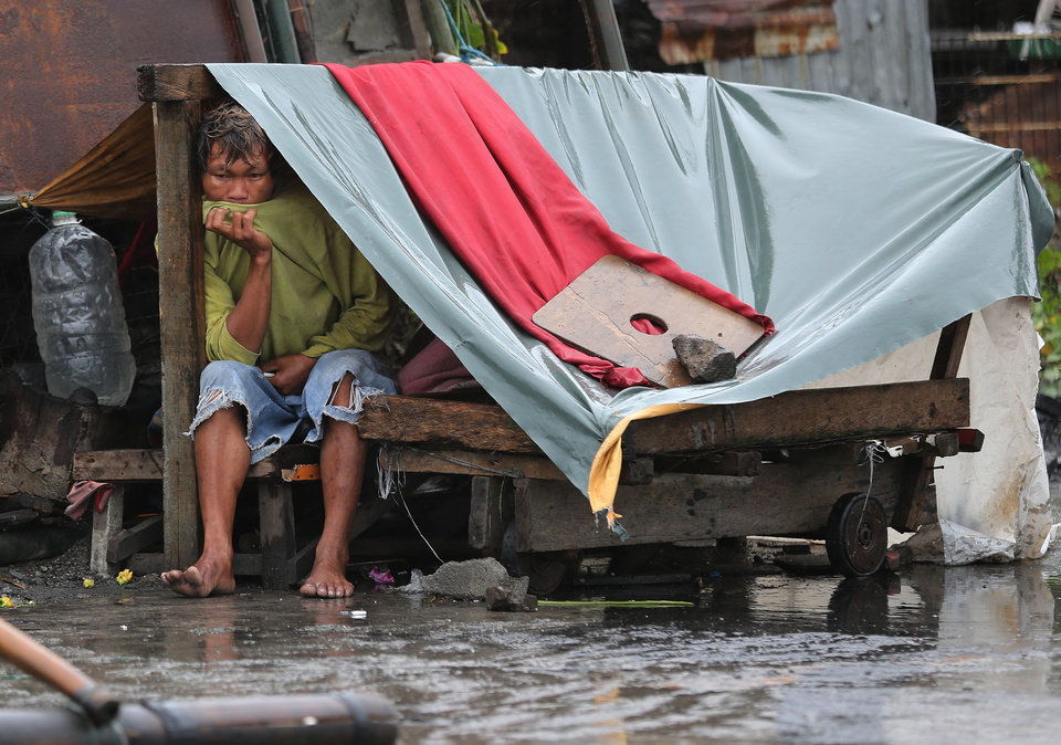 Photo - A Filipino man sits inside his makeshift home as strong winds and rains caused by Typhoon Koppu hits the coastal town of Navotas, north of Manila, Philippines on Sunday, Oct. 18, 2015.  Slow-moving Typhoon Koppu blew ashore with fierce wind in the northeastern Philippines early Sunday, toppling trees and knocking out power and communications. (AP Photo/Aaron Favila)