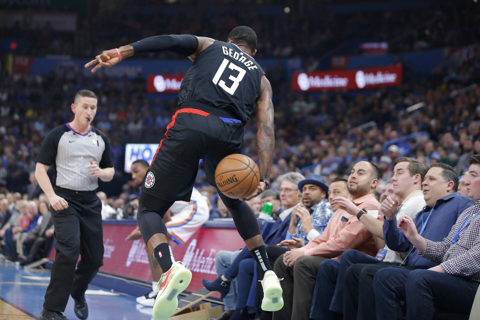 Photo - LA's Paul George (13) saves the ball during an NBA basketball game between the Oklahoma City Thunder and the Los Angeles Clippers at Chesapeake Energy Arena in Oklahoma City, Tuesday, March 3, 2020. [Bryan Terry/The Oklahoman]
