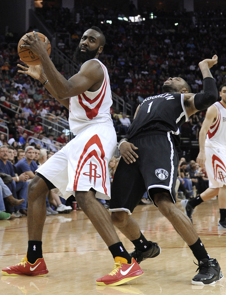 Photo - Brooklyn Nets' C.J. Watson (1) backs away from Houston Rockets' James Harden (13) in the second half of an NBA basketball game Saturday, Jan. 26, 2013, in Houston. The Rockets won 119-106. (AP Photo/Pat Sullivan)
