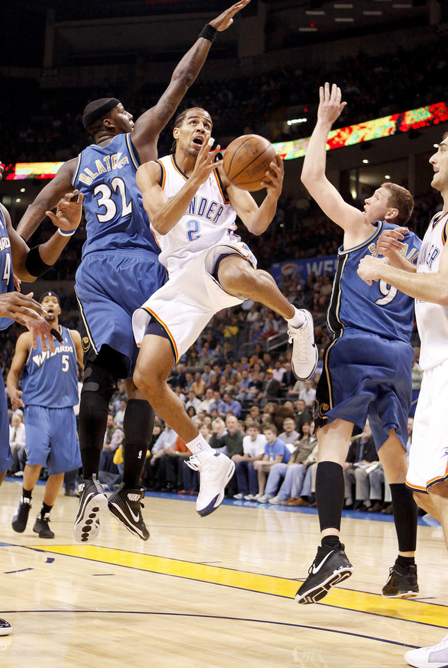 Photo - Oklahoma City's Thabo Sefolosha goes to the basket between Washington's Andray Blatche, left, and Darius Songaila during the NBA basketball game between the Oklahoma City Thunder and the Washington Wizards at the Ford Center in Oklahoma City, Wed., March 4, 2009. PHOTO BY BRYAN TERRY, THE OKLAHOMAN
