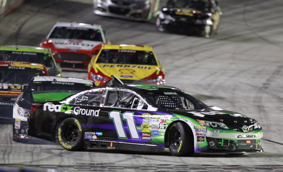 Photo - Driver Denny Hamlin (11) gets turned by driver Kevin Harvick, behind, as they come down the front straight away during a NASCAR Sprint Cup Series auto race at Bristol Motor Speedway on Saturday, Aug. 23, 2014, in Bristol, Tenn. (AP Photo/Wade Payne)
