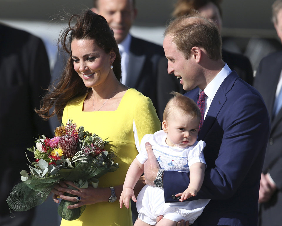 Photo - Britain's Prince William holding his son Prince George and his wife Kate, Duchess of Cambridge, arrive in Sydney Wednesday, April 16, 2014. The royal couple are on a three-week tour of Australia and New Zealand, the first official trip overseas with their son, Prince George. (AP Photo/Rob Griffith)