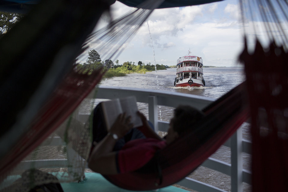 """Photo - In this May 22, 2014, photo, regional boats travel on the Solimoes river near Manaus, Brazil. The lumbering wooden vessels are slow going _ the """"Almirante Barbosa"""" chugs at some 20 kilometers (12 miles) an hour with trips that can stretch out for days or even weeks. (AP Photo/Felipe Dana)"""