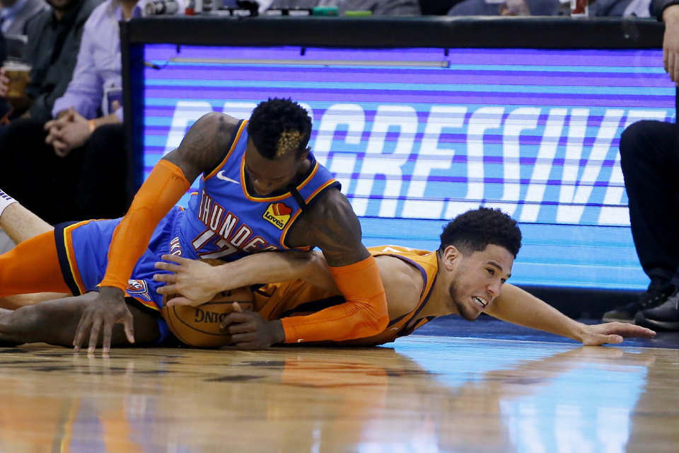 Photo - Phoenix Suns guard Devin Booker, right, dives after a loose ball with Oklahoma City Thunder guard Dennis Schroeder (17) during the second half of an NBA basketball game Friday, Jan. 31, 2020, in Phoenix. The Thunder won 111-107. (AP Photo/Ross D. Franklin)