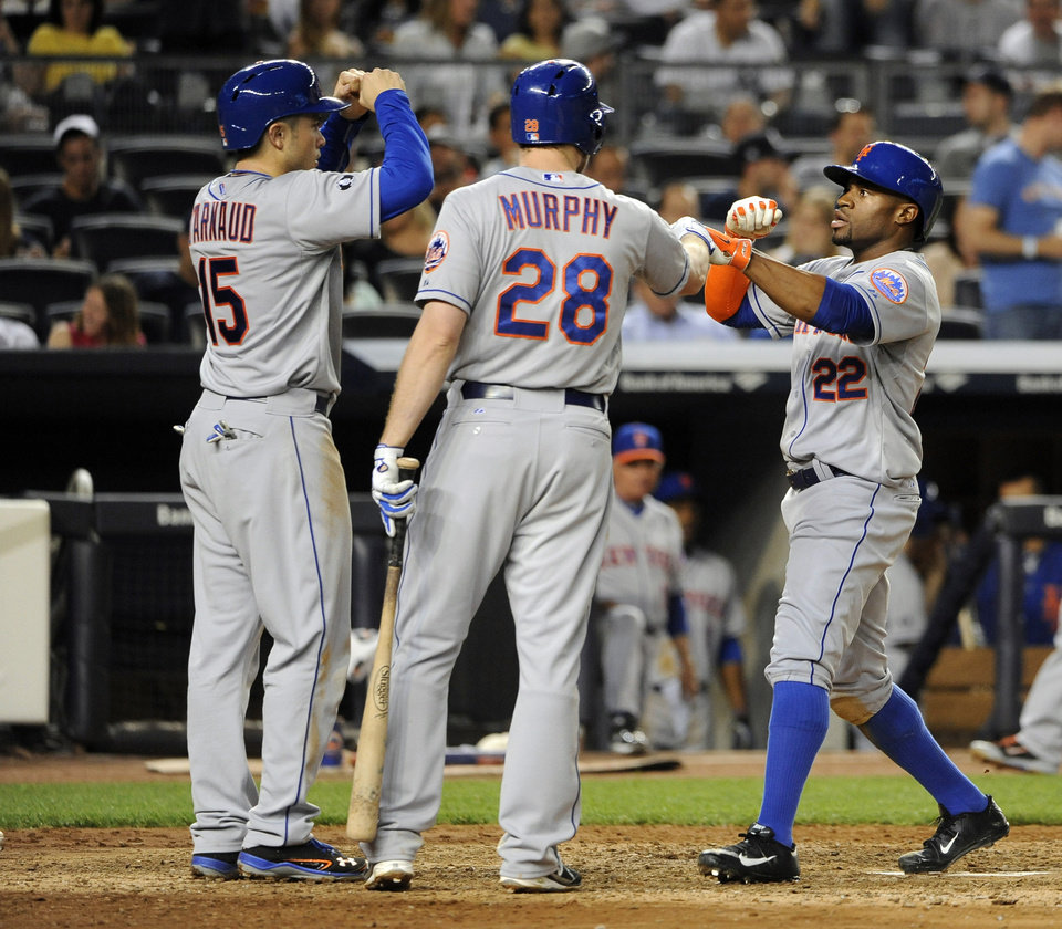 Photo - New York Mets' Eric Young Jr. (22) is greeted at home plate by Travis d'Arnaud (15) and Daniel Murphy (28) after Young hit a two-run home run off of New York Yankees relief pitcher Alfredo Aceves in the seventh inning of an interleague baseball game at Yankee Stadium on Monday, May 12, 2014, in New York. (AP Photo/Kathy Kmonicek)