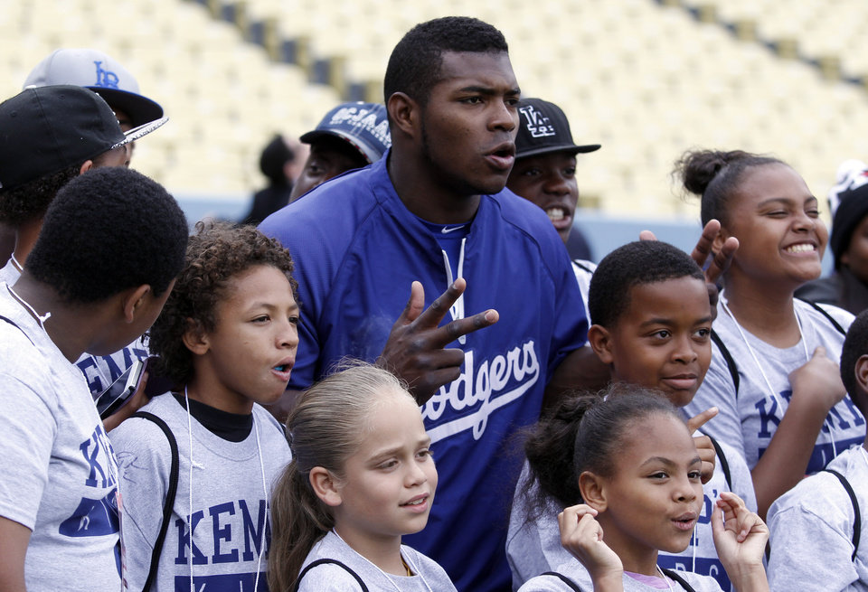 Photo - Los Angeles Dodgers' Yasiel Puig poses for a photograph with Kemp's kids before a baseball game against the Colorado Rockies on Friday, April 25, 2014, in Los Angeles. Dodgers Player Program is established and fully sponsored by Matt Kemp to provide underprivileged and inner-city youth with opportunities to visit and experience Dodger Stadium. (AP Photo/Alex Gallardo)