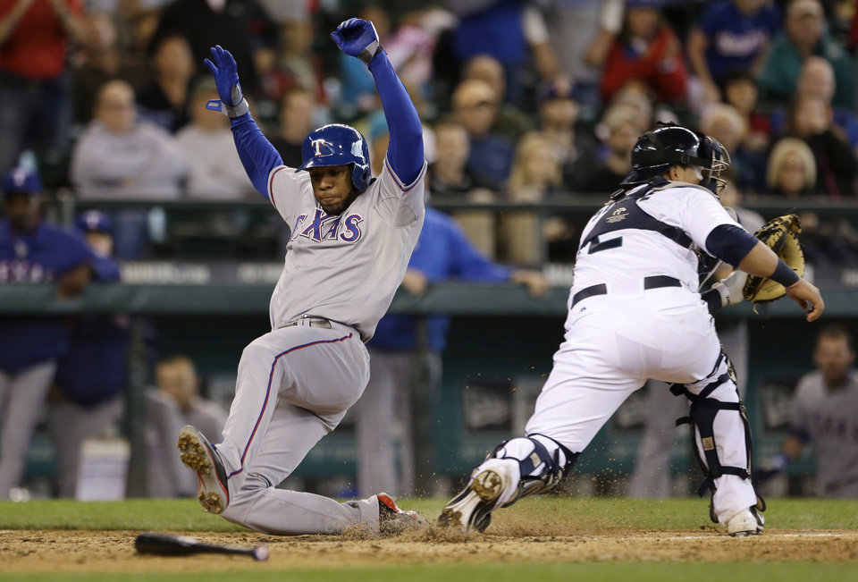 Seattle Mariners catcher Jesus Sucre, right, waits for the throw as Texas Rangers' Elvis Andrus scores in the 11th inning in a baseball game Sunday, May 26, 2013, in Seattle. (AP Photo/Elaine Thompson)