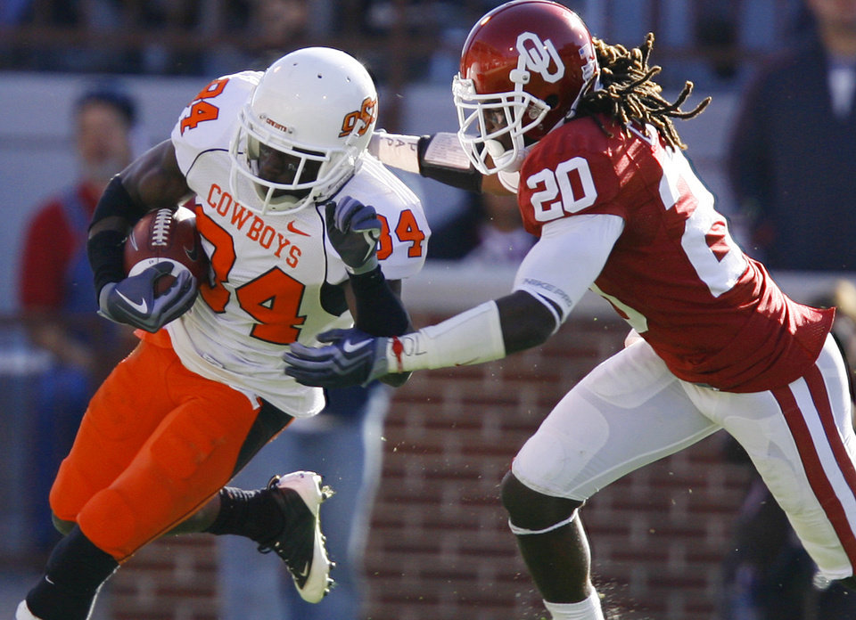 Photo - Oklahoma's Quinton Carter (20) chases down OSU's Hubert Aniam (84) during the second half of the Bedlam college football game between the University of Oklahoma Sooners (OU) and the Oklahoma State University Cowboys (OSU) at the Gaylord Family-Oklahoma Memorial Stadium on Saturday, Nov. 28, 2009, in Norman, Okla.Photo by Chris Landsberger, The Oklahoman