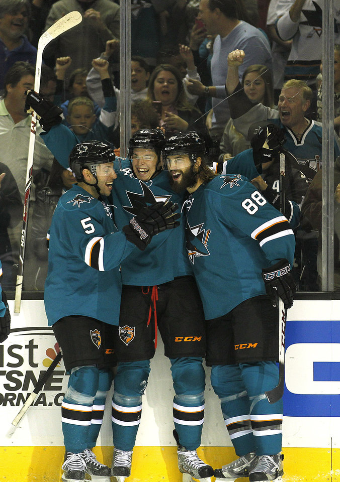 San Jose Sharks center Tomas Hertl, center, celebrates with teammates defenseman Jason Demers (5) and Brent Burns (88) after scoring his second goal against the Phoenix Coyotes during the first period an NHL hockey game in San Jose, Calif., Saturday, Oct. 5, 2013. (AP Photo/Tony Avelar)