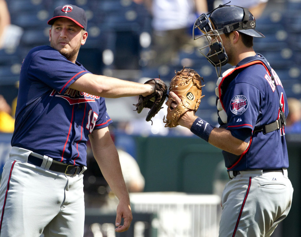Photo -   Minnesota Twins relief pitcher Glen Perkins (15) is congratulated by catcher Drew Butera (41) following a baseball game against the Kansas City Royals at Kauffman Stadium in Kansas City, Mo., Sunday, July 22, 2012. The Twins won 7-5. (AP Photo/Orlin Wagner)