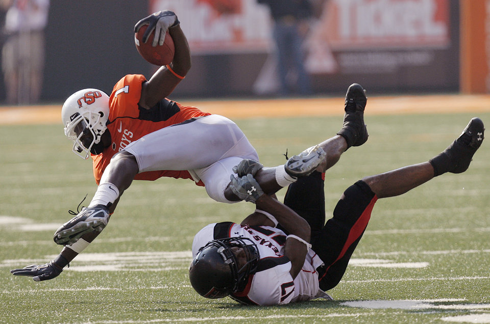 Photo - Oklahoma State's Dez Bryant (1) is tripped up by Texas Tech's Chris Parker (17) during the second half of the college football game between the Oklahoma State University Cowboys (OSU) and the Texas Tech University Red Raiders (TTU) at Boone Pickens Stadium in Stilllwater, Okla., on Saturday, Sept. 22, 2007. OSU won, 49-45. By NATE BILLINGS, The Oklahoman