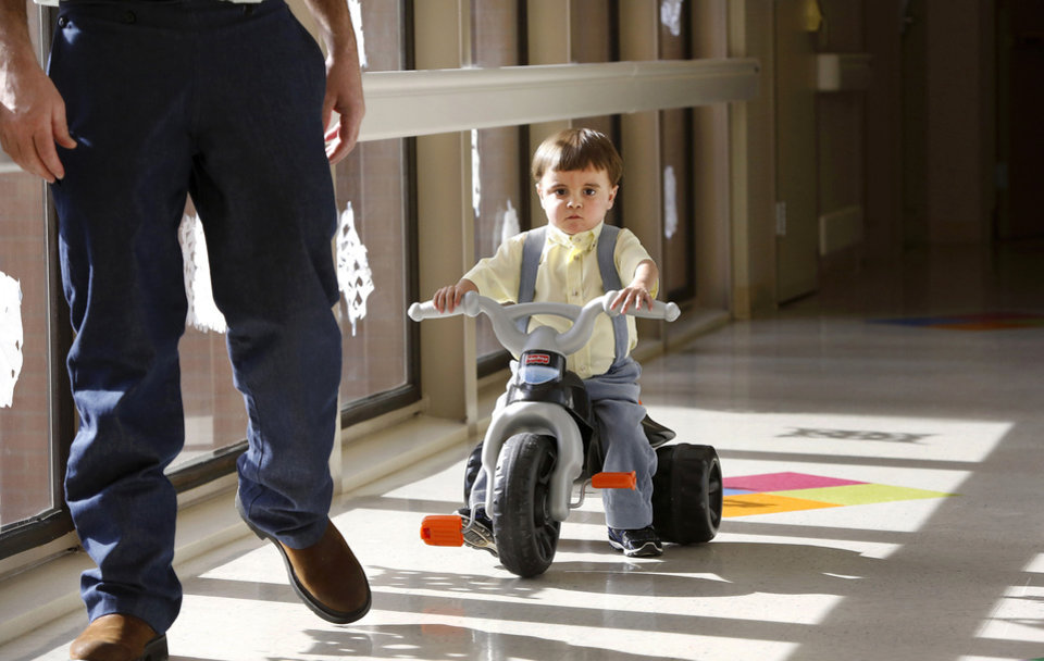 Riding his trike, Troy Yoder, 3, follows his dad Monday down a hallway in the pediatric intensive care unit at Integris Baptist Medical Center. Photos by Jim Beckel, The Oklahoman