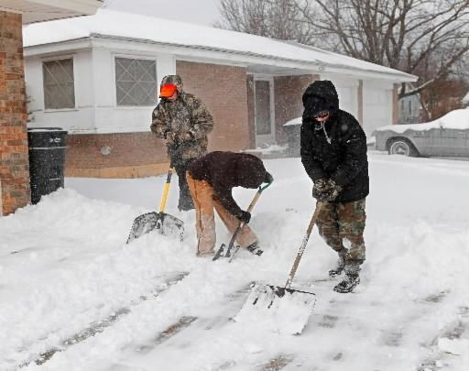 Photo - From left, buddies Tristian Bargewell, 12, James Allison, 11, and Jacob Freitas, 13, grabbed shovels and set out Wednesday morning asking neighbors in their Del City neighborhood to hire the trio to clear snow from their sidewalks and driveways. The boys are pictured clearing a driveway on a street called Wofford. The boys said they teamed last summer to operate a lemonade stand to earn extra spending cash. A second winter storm in a week dumped about 6 inches of snow in the Oklahoma City area Tuesday morning, Feb. 9, 2011. Photo by Jim Beckel