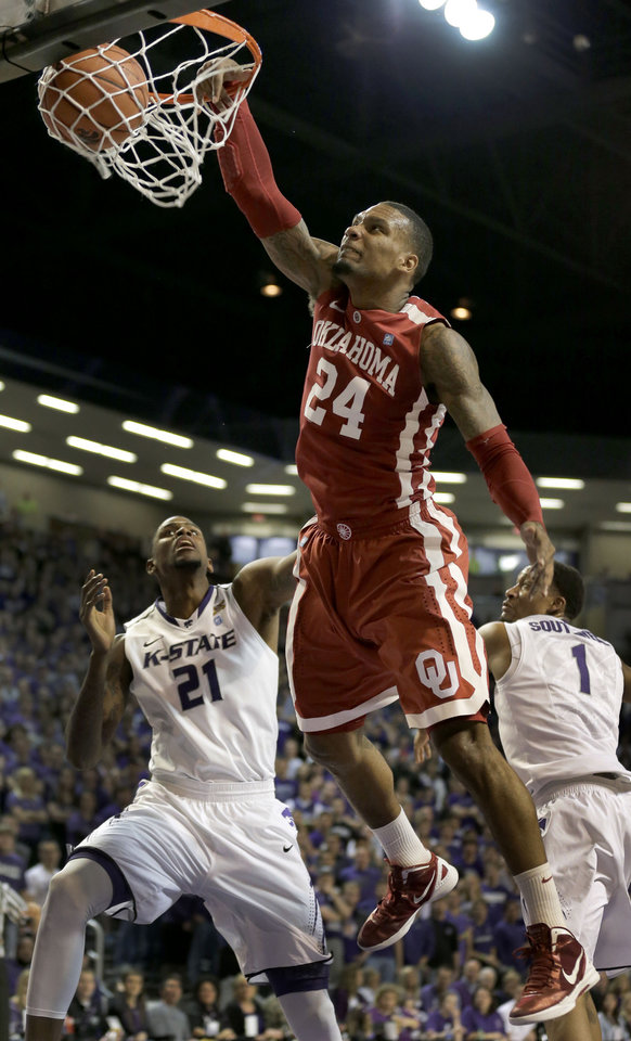 Oklahoma forward Romero Osby (24) gets past Kansas State forward Jordan Henriquez (21) and Kansas State guard Shane Southwell (1) to dunk the ball during the first half of an NCAA college basketball game Saturday, Jan. 19, 2013, in Manhattan, Kan. (AP Photo/Charlie Riedel)