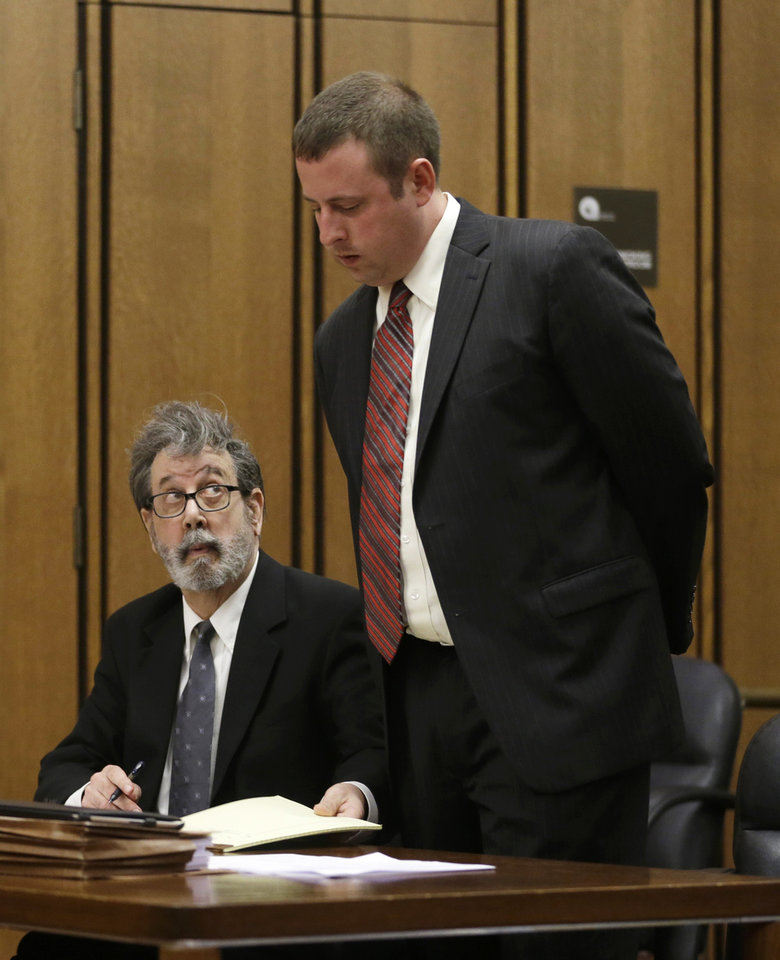 Bobby Thompson, left, looks up at his defense attorney Joseph Patituce as he shows him a paper during court proceedings Monday, Sept. 30, 2013, in Cleveland. Thompson, one-time fugitive heads to trial on charges of masterminding a $100 million multi-state fraud under the guise of helping Navy veterans. The defendant calls himself Bobby Thompson, but authorities identified him as 67-year-old Harvard-trained lawyer and former military intelligence officer John Donald Cody. (AP Photo/Tony Dejak)